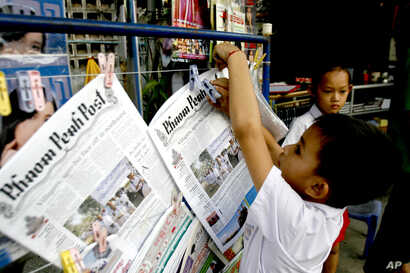 FILE - A boy hangs up copies of the English-language Phnom Penh Post at a newsstand in Phnom Penh, Cambodia, Jan. 8, 2008.