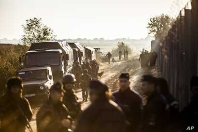 Soldiers and police officers stand beside the border fence between Hungary and Serbia near Roszke, 180 kms southeast from Budapest, Hungary, Sept.14, 2015.