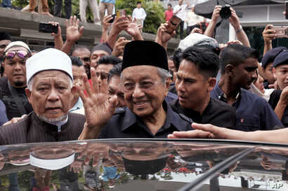 Malaysian Prime Minister Mahathir Mohamad, center, waves to crowds leaving National Mosque after performing Friday prayers in Kuala Lumpur, Malaysia, Friday, May 11, 2018.