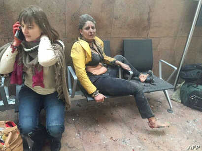 An injured woman looks on as another speaks on her mobile phone following twin blasts at Brussels airport in Zaventem on March 22, 2016 as part of co-ordinated attacks claimed by Islamic State group (IS) millitants at the city's airport and in a Metr...