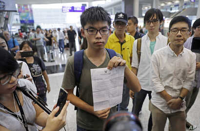 Hong Kong pro-democracy activist Joshua Wong, center, shows the letter from Thailand Immigration office after arriving at Hong Kong airport from Bangkok, Oct. 5, 2016.