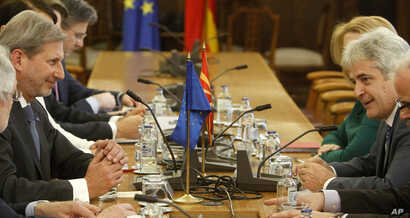 European Union's enlargement commissioner Johannes Hahn, left, talks with Ali Ahmeti, right, the leader of the main ethnic Albanian party DUI, at the parliament building in Skopje, Macedonia, March 21, 2017.