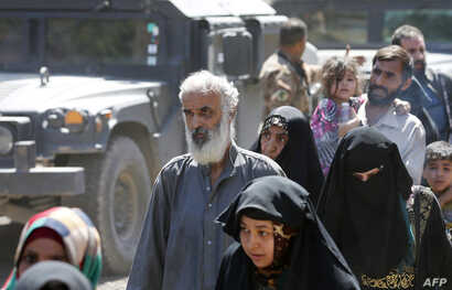 Iraqis leave the Zanjili neighborhood in west Mosul on June 3, 2017, during the ongoing offensive by security forces to retake the city from Islamic State (IS) group fighters.