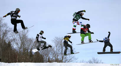 FILE - Snowboarders compete during the men's Snowboard-Cross eighth-finals at the FIS Snowboard World Championships in Stoneham, Quebec, Jan. 26, 2013.