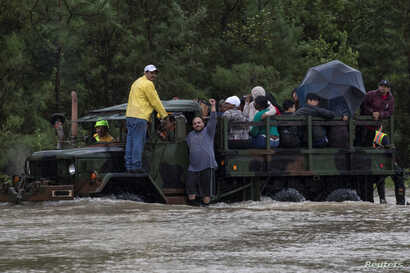 A man wearing a Houston Texans shirt, the local professional American football team, raises his arm as residents are rescued by a truck from floods caused by Tropical Storm Harvey in east Houston, Texas, U.S. August 29, 2017.