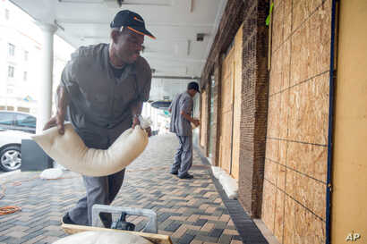 Perry Williams, 47, left, and Alaric Nixon, 28, place sandbags on the storefront of Diamond's International store, in preparation for the arrival of hurricane Joaquin in Nassau, Bahamas, Oct. 1, 2015.