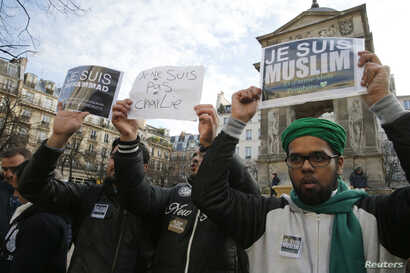 """French Muslim youths hold placards which read, """"I am Muslim. I love my Prophet"""" (R) and """"I am Muhammad. I belong to the Muslim community and I am anti-terrorist"""" during a demonstration in central Paris January 18, 2015. Up to two hundred French Musli..."""