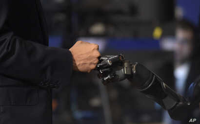 President Barack Obama fist-bumps with Nathan Copeland during a tour of innovation projects at the White House Frontiers Conference at University of Pittsburgh in Pittsburgh, Oct. 13, 2016.