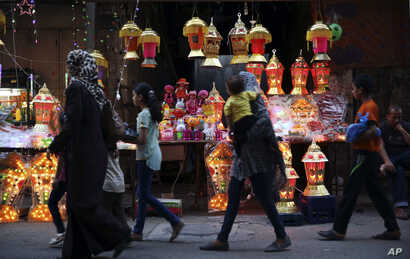 Palestinians walk in front of traditional lighted Ramadan lanterns, marking the holy month of Ramadan at main market in Gaza City, June 3, 2016. Devout Muslims throughout the world will begin to celebrate Ramadan next week, the holiest month in the I...