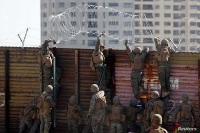 U.S. Marines instal concertina wire along the top of the primary border wall at the port of entry next to Tijuana in San Ysidro, San Diego, California, Nov. 9, 2018.