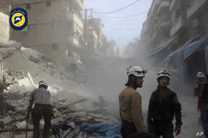 """Aleppo"""" In this picture provided by the Syrian Civil Defense group known as the White Helmets, Syrian Civil Defense workers search through the rubble in rebel-held eastern Aleppo, Syria, Wednesday, Oct. 12, 2016."""