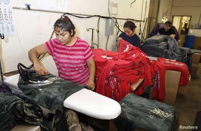 Workers press women's t-shirts after they have been printed with designs at the Sledge USA clothing factory in Los Angeles, California, Oct. 13, 2009.