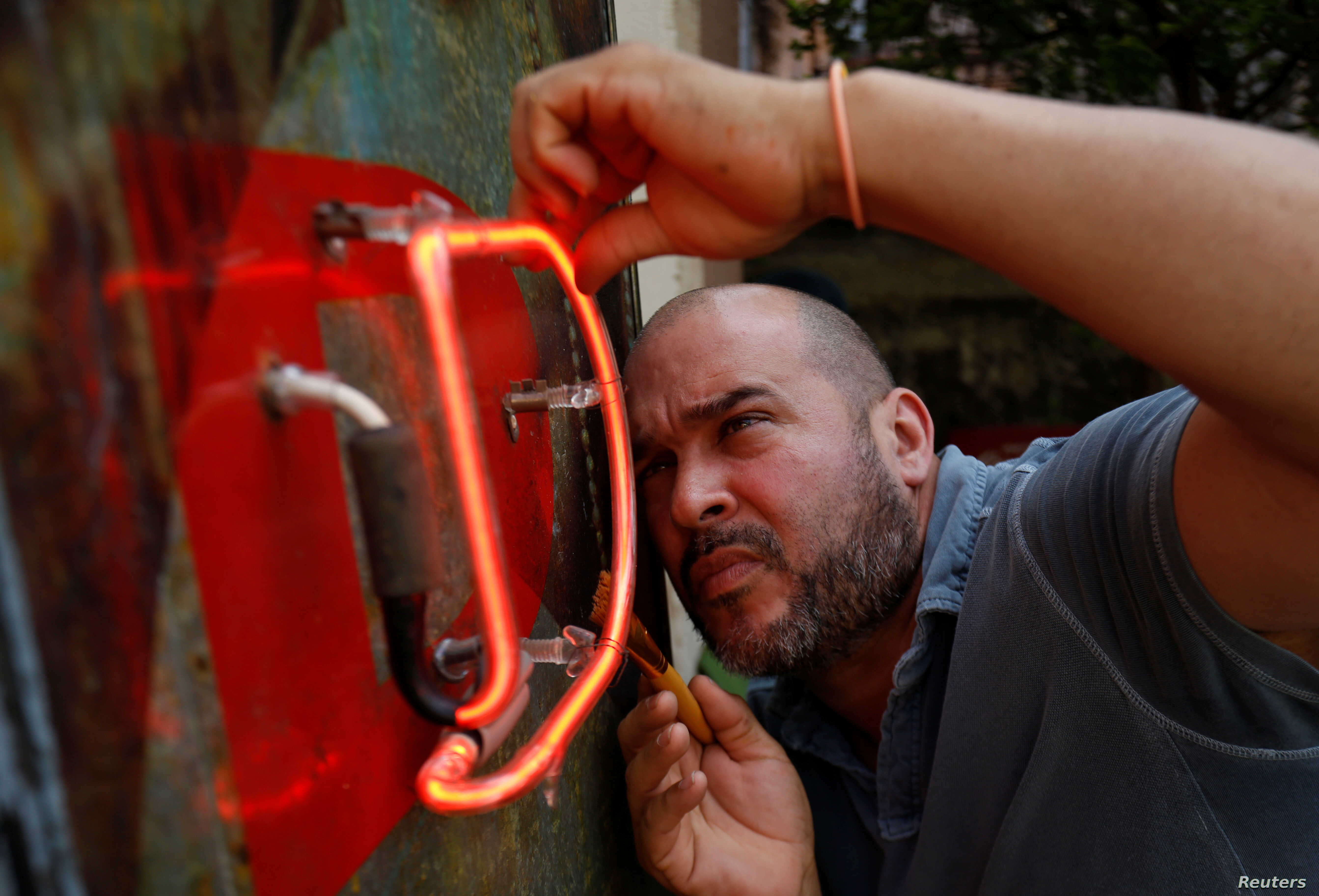 Cuban artist Kadir Lopez Nieves, who is restoring the vintage neon signs of the city, works in his workshop and gallery, in Havana, Cuba, Feb. 19, 2018.