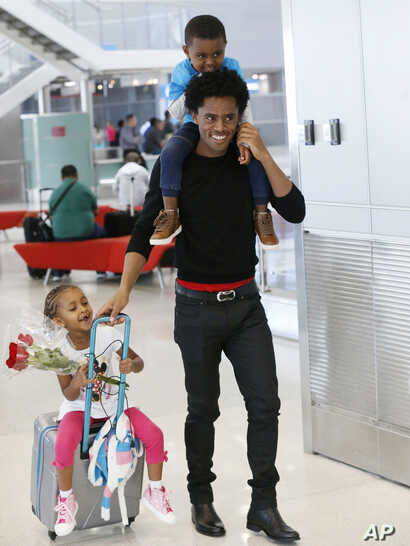 Olympic silver medalist Feyisa Lilesa, of Ethiopia, carries his son Sora, 3, and pulls along his daughter Soko, 5, after picking up his family at Miami International Airport, Feb. 14, 2017.