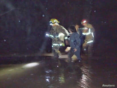 Emergency personnel rescue people from flood waters and debris after a mudslide in Montecito, California, U.S. in this photo provided by the Santa Barbara County Fire Department, Jan. 9, 2018.