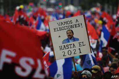 """A supporter of embattled Nicaraguan President Daniel Ortega holds a placard reading """"Let's go to the Polls. (Ortega) Till 2021"""" during the government-called """"Walk for Security and Peace"""" in Managua, July 7, 2018."""