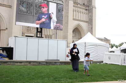 A young family plays alongside the main stage at the start of the One Journey Festival in support of refugees at Washington's National Cathedral, Washington, June 2, 2018, (V. Macchi/VOA)