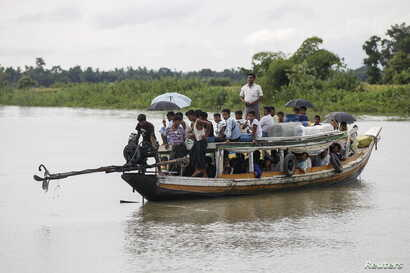 FILE - Rohingya Muslims travel on a boat along a river in Buthidaung township, Myanmar, on June 7, 2015.
