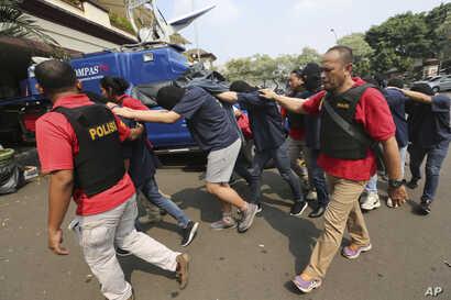 Police officers escort men arrested in a raid on a gay sauna at North Jakarta police headquarters in Jakarta, Indonesia, May 22, 2017. Indonesian police detained dozens of men in a weekend raid on a gay sauna in the capital.