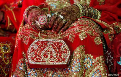 FILE - A bride holds her purse during a mass wedding ceremony in Karachi, Pakistan, May 9, 2016.