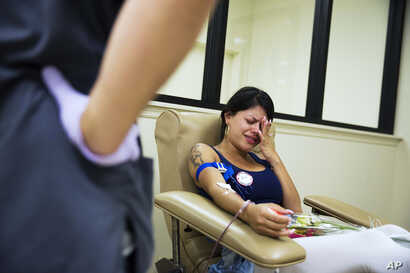 Tatiana Osorio of Orlando, Fla., cries while giving blood at the OneBlood center, near the nightclub where a mass shooting occurred the night before, June 13, 2016. Osorio lost three friends in the shooting.