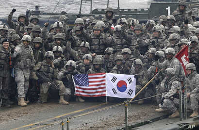 FILE - U.S. and South Korean army soldiers pose on a floating bridge on the Hantan river during a joint military exercise against a possible attack from North Korea, in Yeoncheon, South Korea, Dec. 10, 2015.