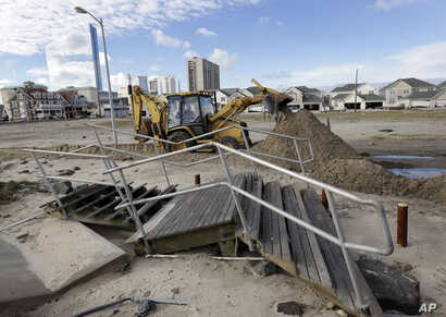A worker uses a backhoe to clear sand and debris that was carried onshore by surge from superstorm Sandy in Atlantic City, N.J., Oct. 31, 2012.