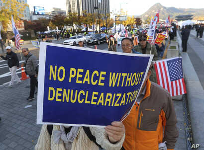 Protesters march toward the U.S. Embassy during a rally supporting the United States' policy to put steady pressure on North Korea in Seoul, South Korea, Nov. 3, 2018. North Korea has warned it could revive a state policy aimed at strengthening its n