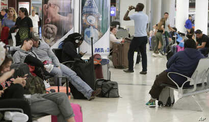 Travelers wait near a closed terminal at the Miami International Airport., Jan. 12, 2019. The partial government shutdown is starting to strain the national aviation system, with unpaid security screeners staying home, air traffic controllers suing t...