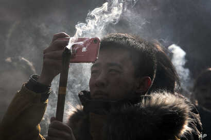 FILE - A Chinese man uses iPhone to take picture as he prays for health and fortune on the first day of the New Year at Yonghegong Lama Temple in Beijing, Jan. 1, 2019.