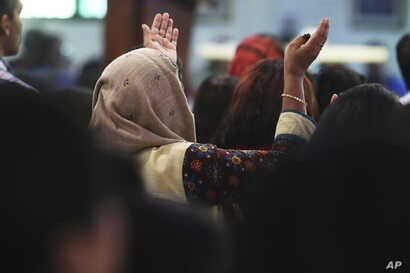 A woman prays during Mass at St. Mary's Catholic Church in Dubai, United Arab Emirates, Sunday, Jan. 20, 2019.