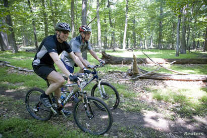FILE - U.S. President George W. Bush and Danish Prime Minister Anders Fogh Rasmussen (left) navigate a path at Camp David presidential retreat, on mountain bikes, June 9, 2006.