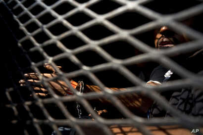 A man who is part of the Central American migrant caravan sits inside a police wagon after being detained for smoking marijuana according to the police, in Tijuana, Mexico, Nov. 21, 2018. The actions of a few appear to be tarnishing the image of the ...