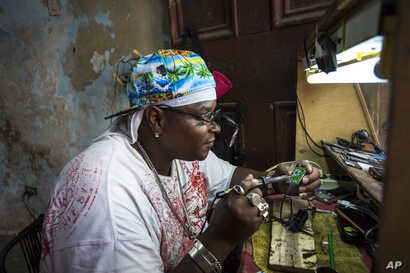 Private jeweler and electronics technician Gabriel La O repairs a mobile phone inside a government store where he rents work space in Havana, May 24, 2016. Cuba says it will legalize small and medium-sized private businesses, adding to the Communist ...