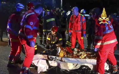 In this frame taken from video, rescuers assist injured people outside a nightclub in Corinaldo, central Italy, early Dec. 8, 2018.