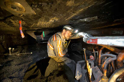 FILE - Scottie Stinson, a coal miner of 16 years, works to secure the roof with bolts in an underground coal mine roughly 40-inches-high in Welch, W.Va.