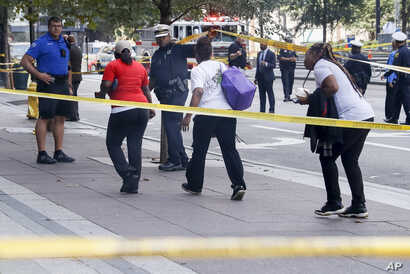 Pedestrians are allowed to exit police cordons as emergency personnel and police work the scene of shooting near Fountain Square, Sept. 6, 2018, in downtown Cincinnati.
