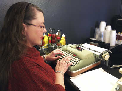 """Andrea Kittle of Albuquerque, N.M., tries out a vintage Smith Corona electric typewriter at a """"type-in"""" in Albuquerque, April 23, 2017."""