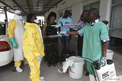 FILE - A health worker sprays a colleague with disinfectant during a training session for Congolese health workers to deal with Ebola virus in Kinshasa, Oct. 21, 2014. The Democratic Republic of Congo had declared a two-month ebola outbreak over.