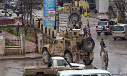 An image grab taken from a video obtained by AFPTV, Jan. 16, 2019, shows U.S. troops gathered at the scene of a suicide attack in the northern Syrian town of Manbij.