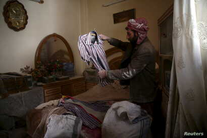 A man inspects a shirt of his dead son, who died yesterday, after an airstrike in the rebel-held besieged city of Douma, a suburb of Damascus, Syria, Feb. 27, 2016.