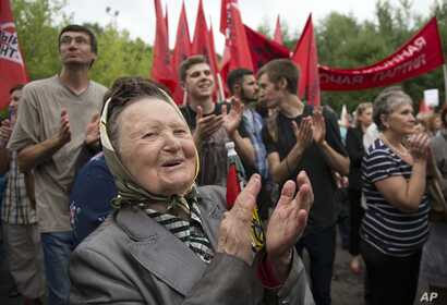 People applaud a speaker during a protest against raising the retirement age and reforming the pension system, at Sokolniki Park, in Moscow, Russia, July 18, 2018.