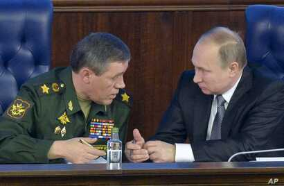 Russian President Vladimir Putin, right, speaks with Chief of the General Staff of the Russian Armed Forces Valery Gerasimov at a meeting with top military officials in the National Defense Control Center in Moscow, Russia, Dec. 11, 2015.