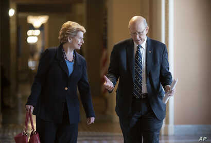 Ranking member Sen. Debbie Stabenow, D-Mich., left, ranking member of the Senate Agriculture Committee, and Sen. Pat Roberts, R-Kan., the chairman, walk to the chamber at the Capitol in Washington, April 26, 2018.
