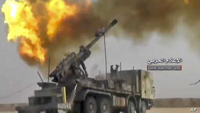 FILE - Photo taken from video provided by the government-controlled Syrian Central Military Media shows firing on militants' positions on the Iraq-Syria border, Nov 8, 2017. The Britain-based Syrian Observatory for Human Rights said Islamic State mil...