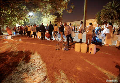 In Cape Town, South Africa, Jan. 25, 2018, People wait their turn to take water from a spring in the Newlands suburb as fears over the city's water crisis grow.