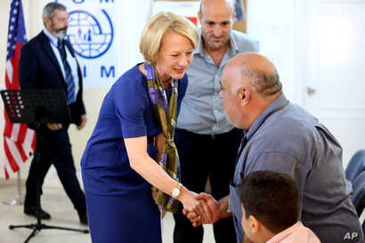 The U.S. ambassador to Jordan, Alice Wells, shakes hands with Syrian refugees ahead of their departure to the United States, Aug. 28, 2016.