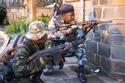 """Kenya security personnel take cover outside the Westgate Mall after shooting started inside the mall early Monday morning, Sept. 23, 2013. Kenya's military launched a major operation at the upscale Nairobi mall and said it had rescued """"most"""" of the h"""