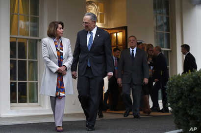 House Democratic leader Nancy Pelosi of California, left, walks with Senate Minority Leader Chuck Schumer, D-N.Y., as Democratic leaders including Sen. Dick Durbin, D-Ill., at right, arrive to speak to the media after meeting with President Donald Tr...
