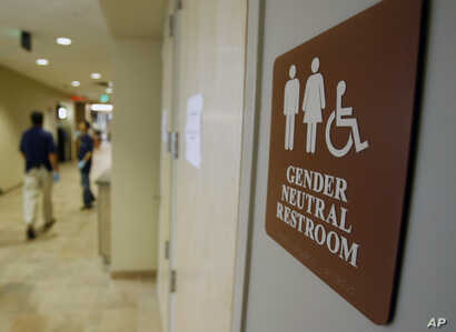 FILE- A sign marks the entrance to a gender-neutral restroom at the University of Vermont in Burlington, Vermont.